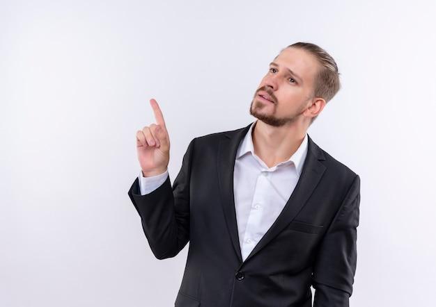 Bel homme d'affaires portant costume à côté avec une expression pensive pointant avec le doigt debout sur fond blanc