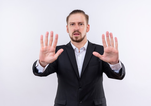 Bel homme d'affaires portant costume faisant panneau d'arrêt avec les mains ouvertes regardant la caméra avec un visage sérieux debout sur fond blanc