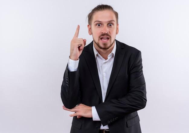 Bel homme d'affaires portant costume montrant l'index à la surprise d'avoir une excellente nouvelle idée debout sur fond blanc