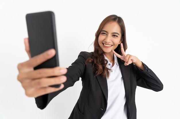 Bel homme d'affaires portant un costume noir souriant lors de la prise de selfie à l'aide d'un appareil photo de téléphone portable