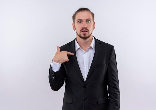 Bel homme d'affaires portant costume pointant avec le doigt sur lui-même à la surprise debout sur fond blanc