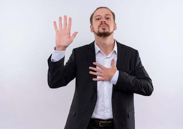 Bel homme d'affaires portant un costume prêtant serment à la confiance debout sur fond blanc