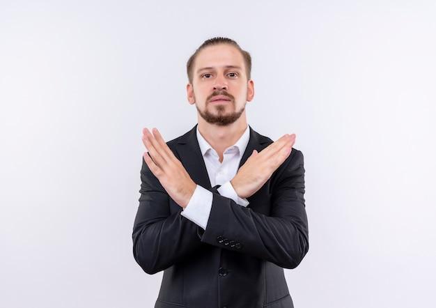 Bel homme d'affaires portant costume regardant la caméra avec les bras croisés faisant panneau d'arrêt avec un visage sérieux debout sur fond blanc