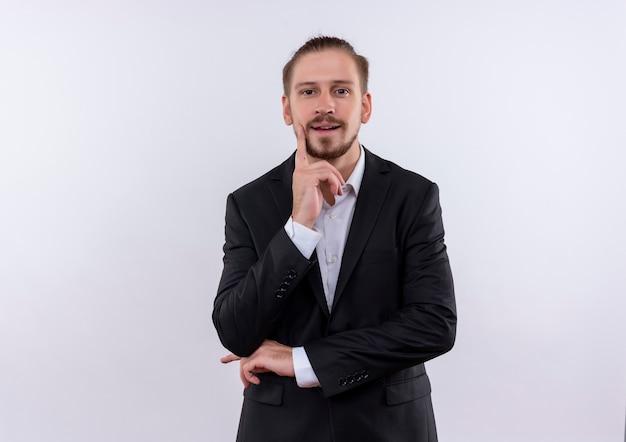 Bel homme d'affaires portant costume regardant la caméra avec une expression pensive pensée positive debout sur fond blanc