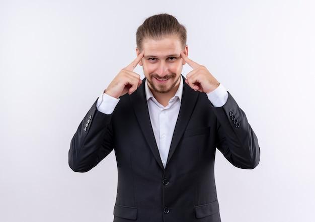Bel homme d'affaires portant costume regardant la caméra avec le sourire sur le visage pointant ses tempes concentré sur la tâche debout sur fond blanc