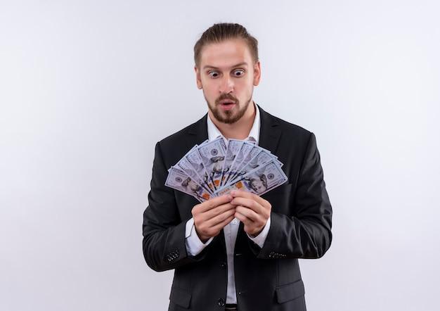 Bel homme d'affaires portant costume tenant de l'argent à la surprise et étonné debout sur fond blanc