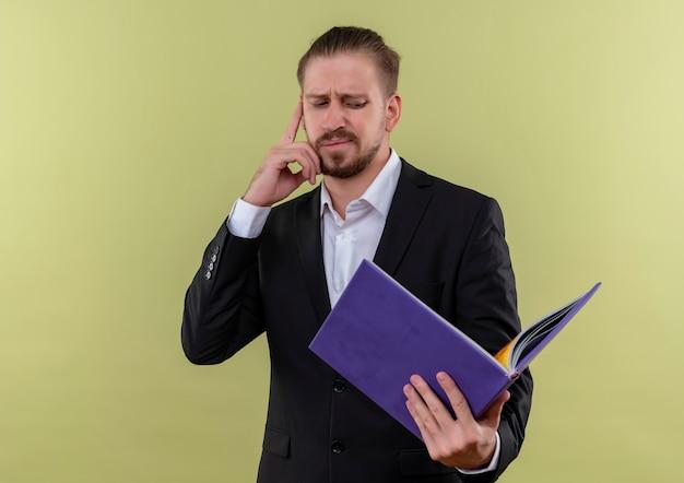 Bel homme d'affaires portant un costume tenant un dossier bleu regardant confus et perplexe debout sur fond vert