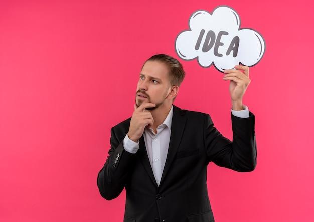 Bel homme d'affaires portant costume tenant mot idée dans une bulle de dialogue à côté perplexe debout sur fond rose
