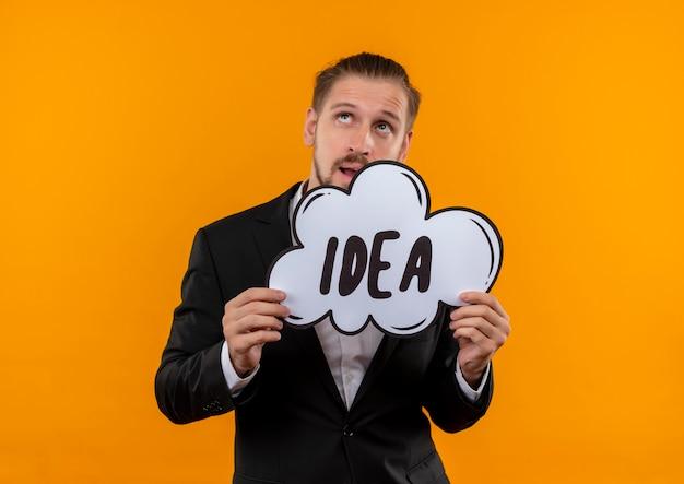 Bel homme d'affaires portant costume tenant mot idée dans une bulle de dialogue à la perplexité debout sur fond orange