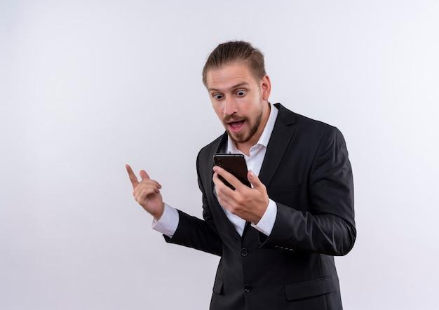Bel homme d'affaires portant costume tenant le smartphone à la surprise et étonné debout sur fond blanc