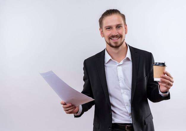Bel homme d'affaires portant costume tenant une tasse de café et des pages blanches regardant la caméra en souriant joyeusement debout sur fond blanc