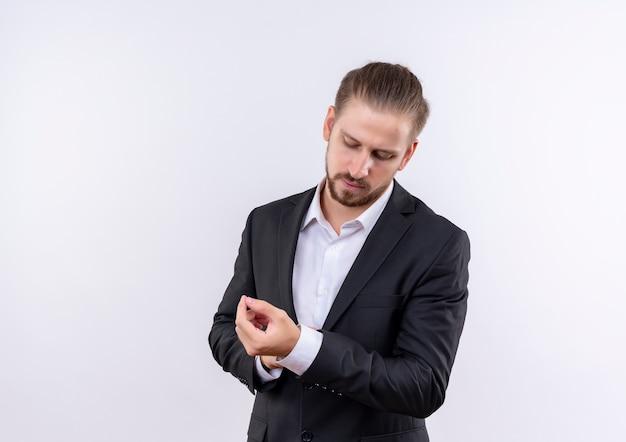 Bel homme d'affaires portant un costume touchant ses boutons de manchette avec un visage sérieux debout sur fond blanc
