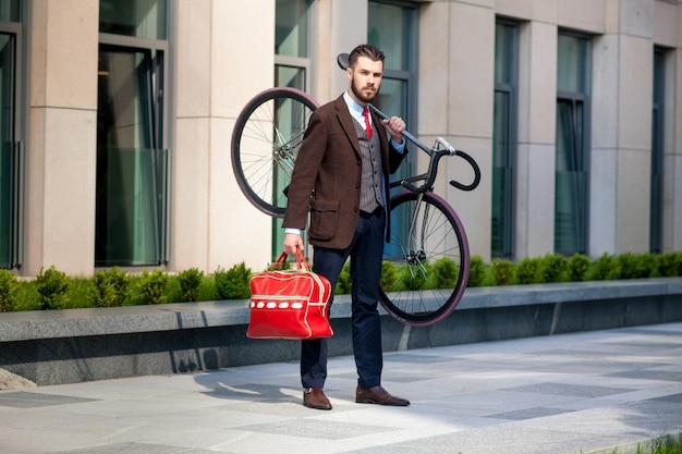 Bel homme d'affaires portant son vélo au bureau