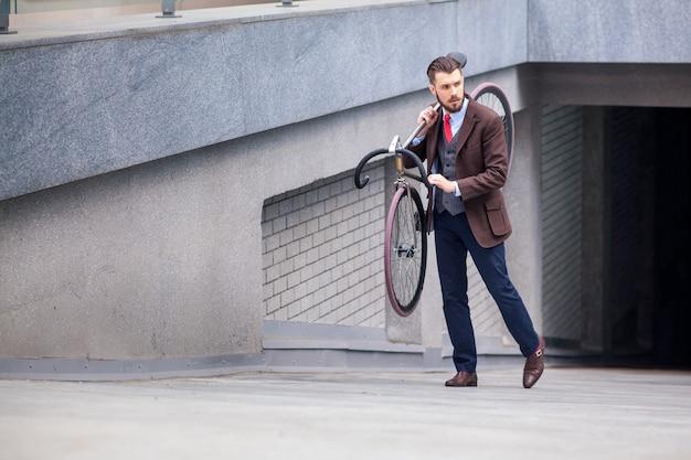 Bel homme d'affaires portant son vélo dans les rues de la ville. le concept du mode de vie moderne des jeunes hommes