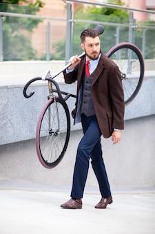 Bel homme d'affaires portant son vélo