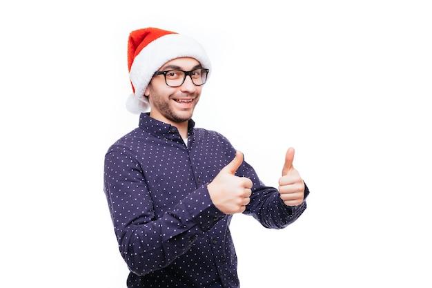 Un bel homme d'affaires porte un bonnet de noel montrant le pouce vers le haut sur un mur isolé blanc