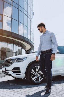 Bel homme d'affaires près de la voiture blanche