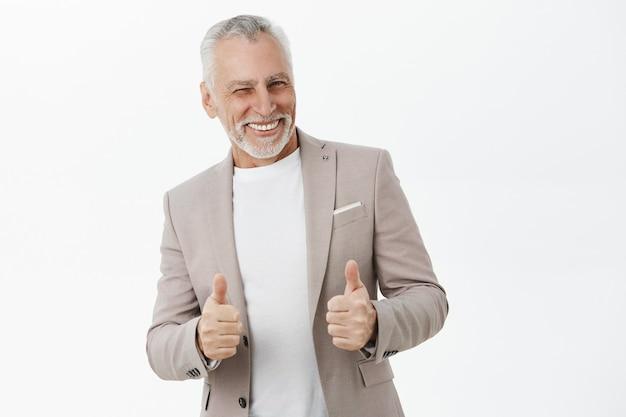 Bel homme d'affaires prospère souriant, montrant le pouce en l'air en approbation