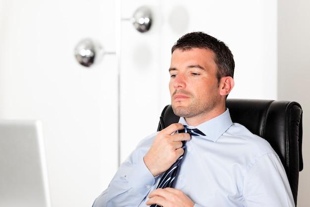 Bel homme d'affaires réajustant sa cravate au bureau