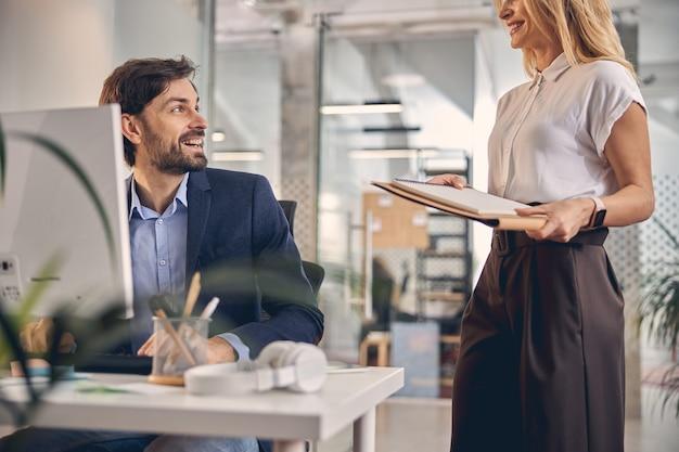Bel homme d'affaires regardant une charmante dame et souriant tout en étant assis à la table avec un ordinateur au bureau