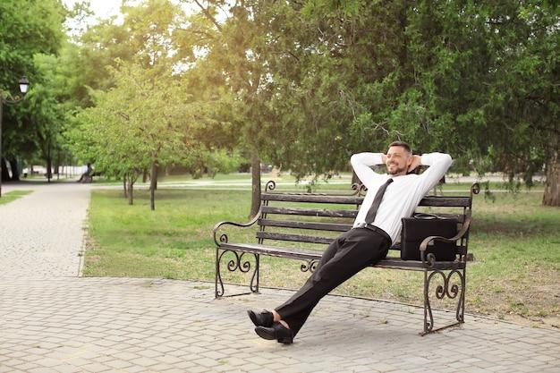 Bel homme d'affaires relaxant dans le parc