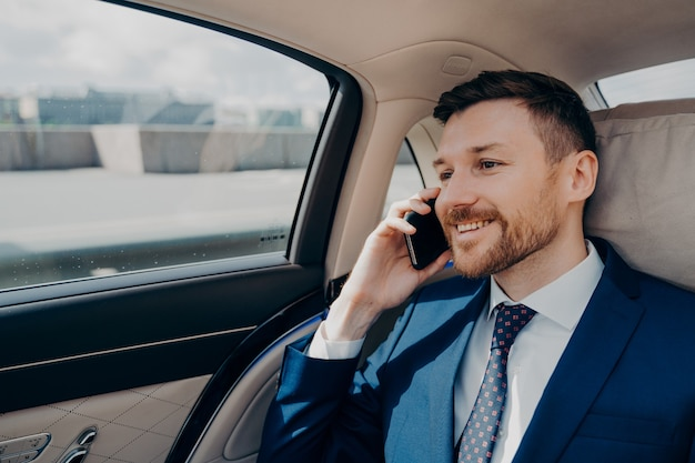 Bel homme d'affaires satisfait assis sur le siège arrière d'une voiture confortable et parlant au téléphone avec son partenaire, jeune homme professionnel entendant de bonnes nouvelles sur un smartphone en automobile