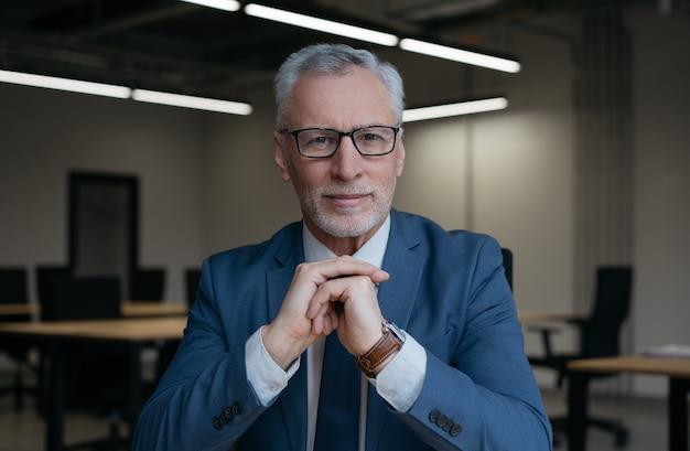 Bel homme d'affaires senior ayant un appel vidéo, réunion en ligne
