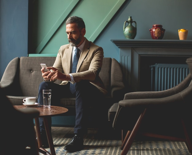 Bel homme d'affaires senior, boire du café et utiliser un téléphone portable dans le hall