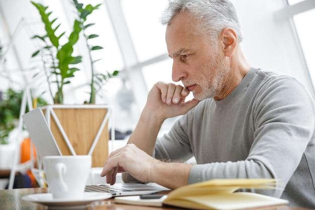 Un bel homme d'affaires senior mature concentré s'asseoir dans un café à l'aide d'un ordinateur portable.
