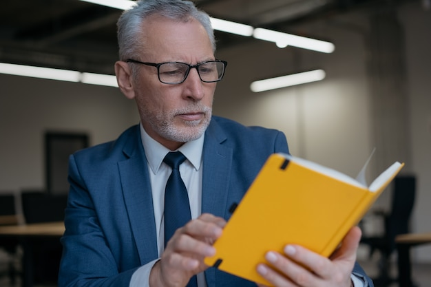 Bel homme d'affaires senior portant des lunettes, livre de lecture, projet de planification, travaillant au bureau