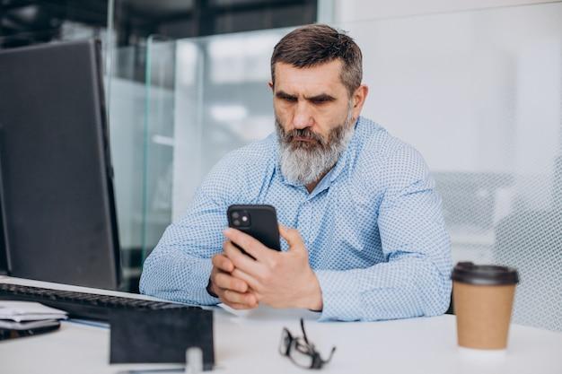 Bel homme d'affaires senior travaillant sur l'ordinateur au bureau
