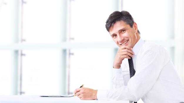 Bel homme d'affaires souriant au bureau