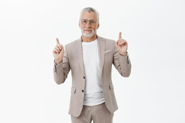Bel homme d'affaires souriant à lunettes et costume pointant les doigts vers le haut, montrant la publicité