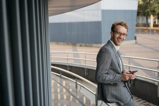 Bel homme d'affaires souriant portant des lunettes de costume utilisant la communication par téléphone portable en ligne