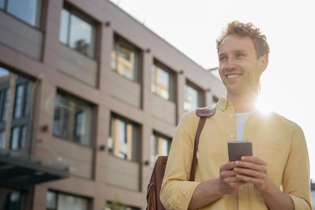 Bel homme d'affaires souriant utilisant un téléphone portable faisant des achats en ligne dans la rue