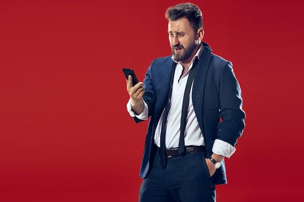 Bel homme d'affaires avec téléphone mobile. homme d'affaires heureux debout isolé sur fond de studio rouge. beau portrait mâle demi-longueur. émotions humaines, concept d'expression faciale.