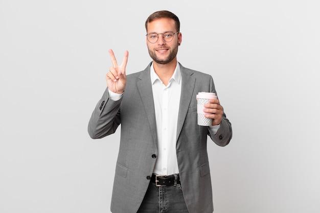 Bel homme d'affaires tenant un café à emporter