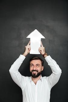 Bel homme d'affaires tenant un pointeur de flèche de discours vide dirigeant vers le haut au-dessus de sa tête, isolé sur l'espace de copie gris foncé