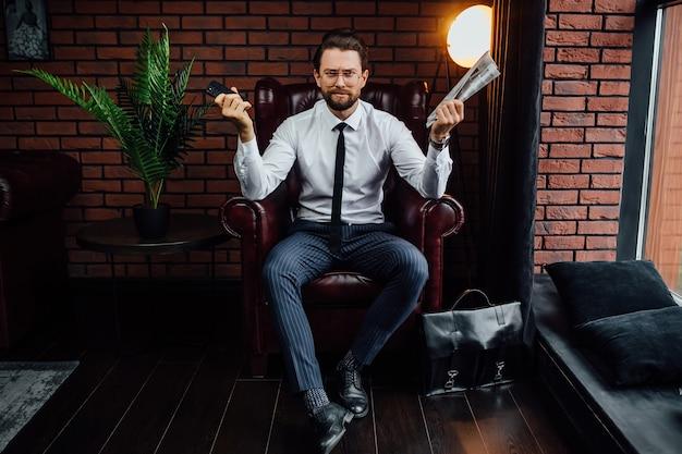 Bel homme d'affaires tenant son smartphone et son journal assis sur un fauteuil.