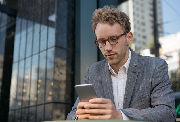 Bel homme d'affaires travaillant à l'aide de la communauté de messagerie texte de téléphone portable en ligne lisant des nouvelles