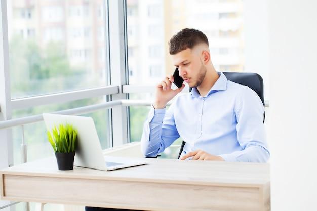 Bel homme d'affaires travaillant avec un ordinateur portable au bureau.