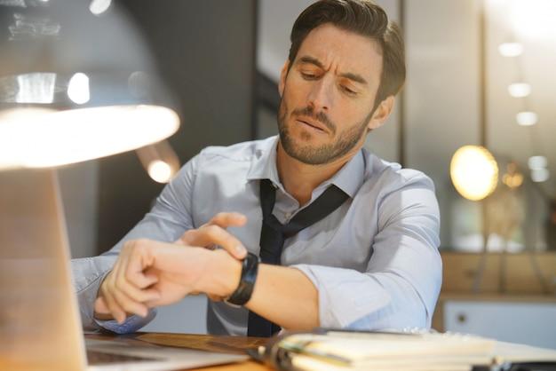Bel homme d'affaires travaillant tard dans la nuit au bureau moderne