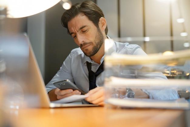 Bel homme d'affaires travaillant tard vérifiant téléphone portable au bureau moderne