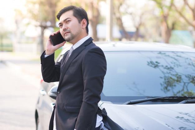 Bel homme d'affaires en utilisant un téléphone portable qui se trouve sur sa voiture