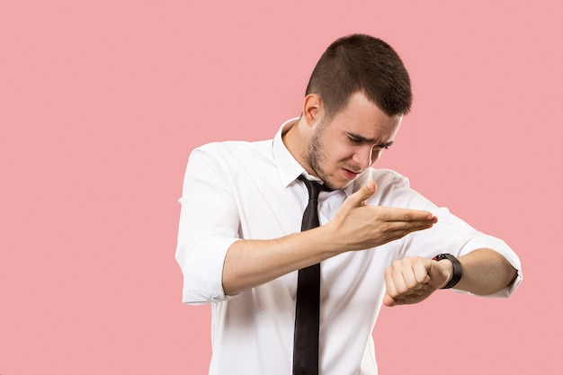 Bel homme d'affaires vérifiant sa montre-bracelet isolée sur fond rose.
