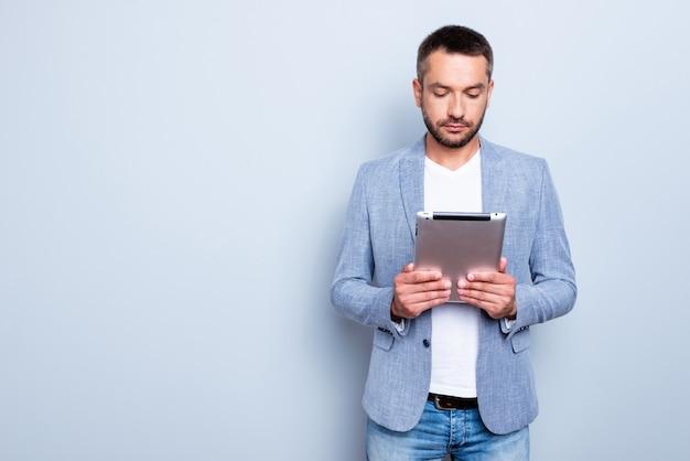 Bel homme d'affaires avec une veste bleue posant contre le mur bleu clair