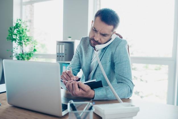 Bel homme d'affaires avec une veste bleue travaillant au bureau