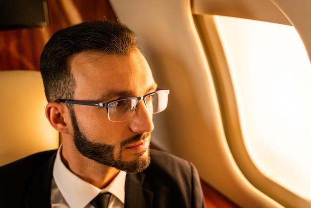 Bel homme d'affaires vêtu d'un costume élégant volant sur jet privé exclusif