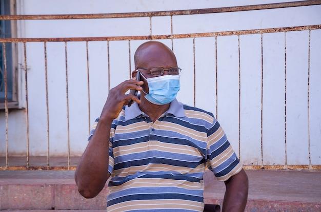 Un bel homme africain âgé portant un masque facial empêchant, s'est empêché de l'épidémie dans la société, se sentant enthousiasmé par l'appel qu'il passe avec son téléphone portable.