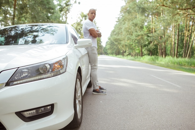 Bel homme africain, appréciant voyager en voiture sur un roadtrip